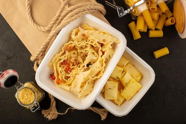 Een deegmaaltijd bovenaanzicht met gedroogde groene kruiden in witte kommen en verpak rauwe italiaanse pasta op donker