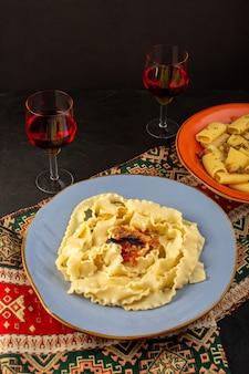 Een deegpasta van bovenaanzicht gekookt smakelijk gezouten binnen ronde blauwe plaat met glazen wijn op ontworpen tapijt en donker bureau