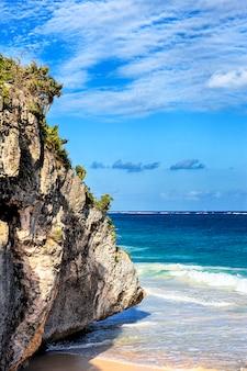 Een deel van caraïbisch strand met grote rots op het zand