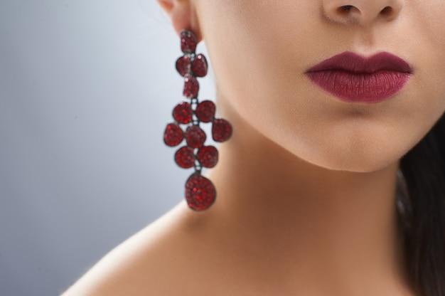 Een deel van de avondlook van een mooi meisje. ze draagt felle bordeauxrode lippenstift en lange luxe oorbellen. de huidskleur van het model is gelijk en gezond. er werd een portret gemaakt