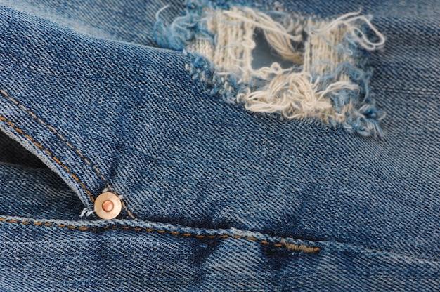 Een deel van de blauwe spijkerbroek met zakken en klinknagels, close-up