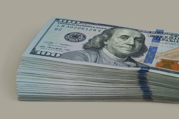 Een deel van de bundel met een wisseling van honderd dollar. op een grijze achtergrond. bekijk schuin.