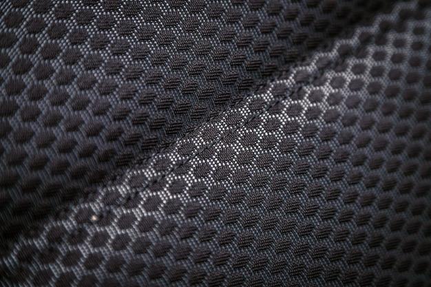 Een deel van de details van de autohoofdsteun. zwart geperforeerde textiel-autostoel als achtergrond. stof textuur