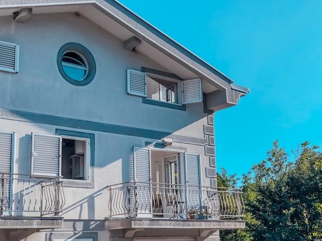 Een deel van de gevel van een huis in moderne stijl tegen de blauwe lucht.