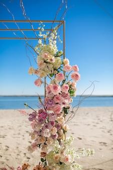 Een deel van de huwelijksboog versierd met verse bloemen ligt aan de blauwe hemel b
