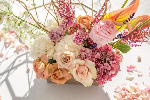 Een deel van de huwelijksboog versierd met verse bloemen ligt aan de zandige oever van de rivier. bruiloft bloemist regelt de workflow