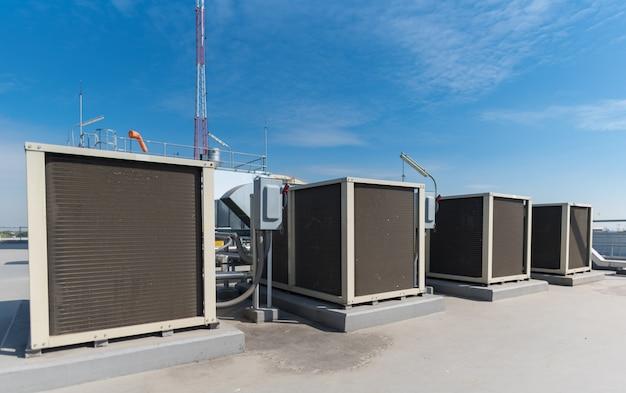 Een deel van de luchtcompressormachine van airconditionersysteem op dakterras met hemelachtergrond.