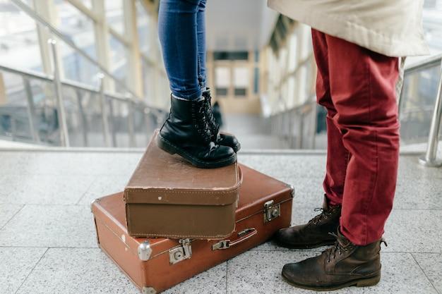 Een deel van de man tot diep in de jeans van bourgondië staat voor de vrouw in een spijkerbroek en zwarte laarzen