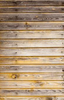 Een deel van de oude houten muur van het gebouw, lang geleden in geel geverfd, geen verf, details van rustieke constructie