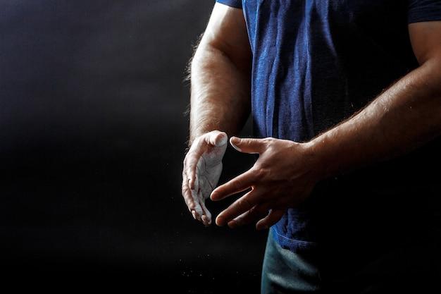 Een deel van de romp van de man, draag een zwart t-shirt met handen bedekt met talkpoeder