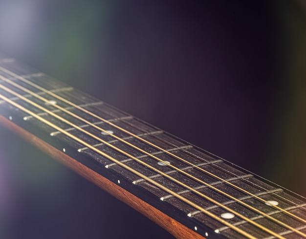 Een deel van een akoestische gitaar, gitaar toets met snaren op een zwarte achtergrond met hoogtepunten.