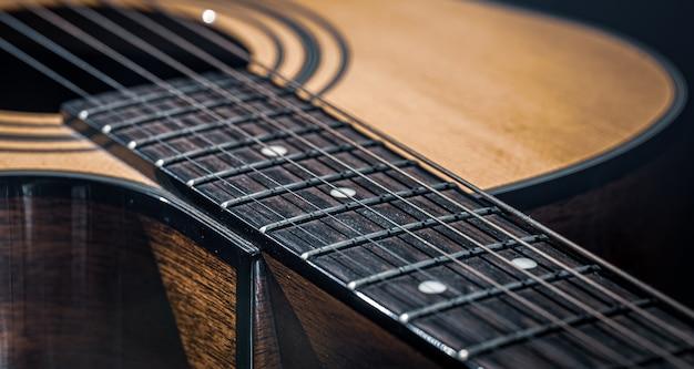 Een deel van een akoestische gitaar, gitaar toets met snaren op een zwarte achtergrond.