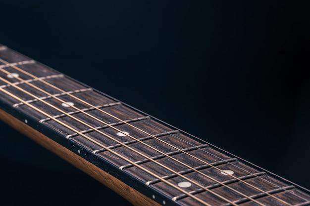Een deel van een akoestische gitaar, gitaar toets op een zwarte achtergrond.