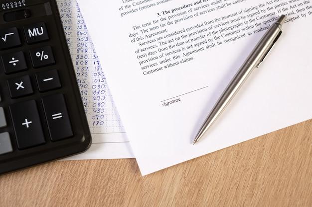 Een deel van een contract of overeenkomst, een ruimte voor ondertekening met een zilveren pen en rekenmachine.