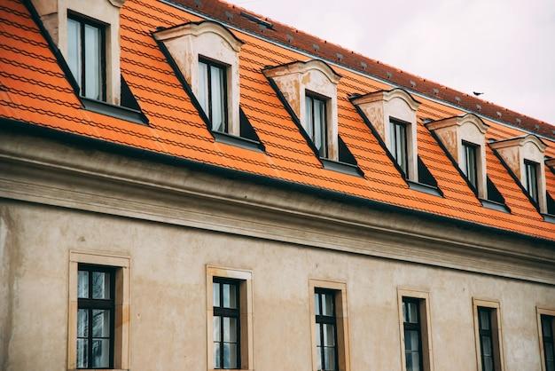 Een deel van een europese gevel met ramen en bakstenen dak.