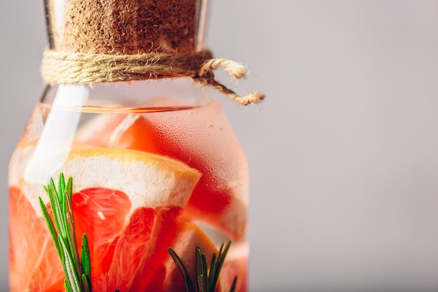Een deel van een fles met water van grapefruit en rozemarijn. detailopname. kopieer de ruimte aan de rechterkant.