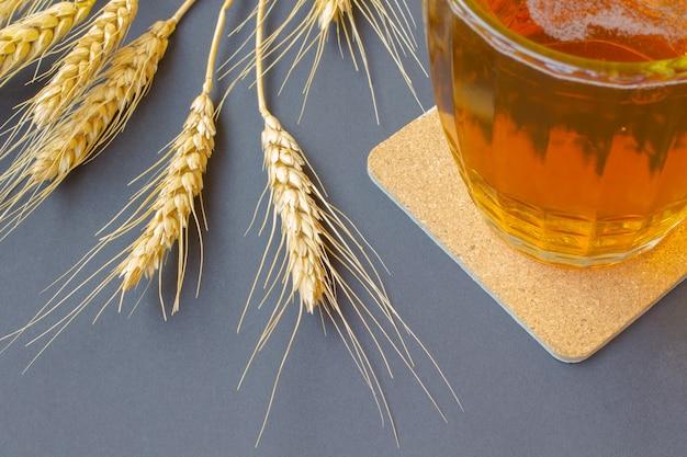 Een deel van een glasmok met bier. oren van tarwe