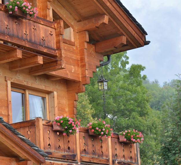 Een deel van een houten chalet in traditionele alpine architectuur in de zomer