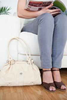 Een deel van een knappe vrouw op een bank met een zak en een tijdschrift
