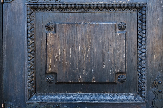 Een deel van een oude houten deur met een gebrandschilderd glaspatroon.