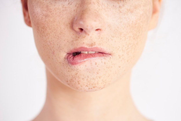 Een deel van een vrouw die op haar lip bijt
