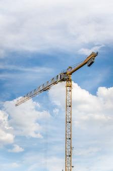 Een deel van geel de kraanwapen van de bouwtoren tegen blauwe hemel