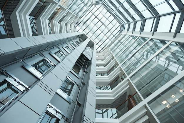 Een deel van het interieur van een modern hoog kantoorgebouw met bewegende lift die als achtergrond kan worden gebruikt