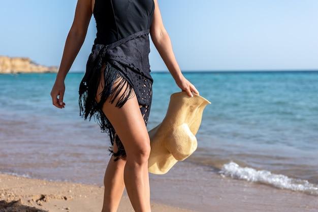 Een deel van het lichaam van een vrouw die op een hete zomerdag langs de kust loopt.