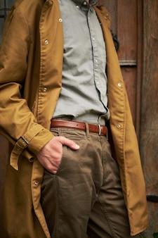 Een deel van het menselijk lichaam draagt een grijs shirt en houdt zijn hand in de zakken van een bruine jas,