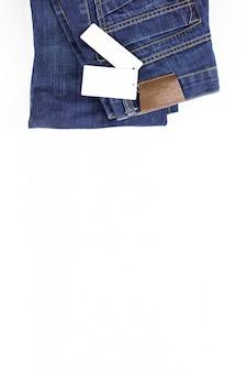 Een deel van jeans die op witte achtergrond met prijskaartje ligt. kleding, online winkelconcepten kopieer de ruimte.