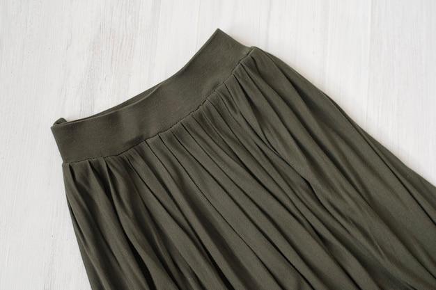 Een deel van kaki rok op houten achtergrond. modieus concept. details