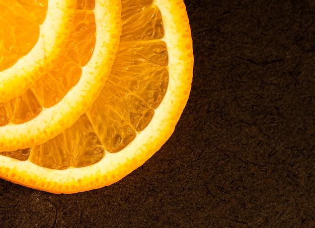 Een deel van sinaasappelplakken op een bruine plaats als achtergrond voor uw tekst