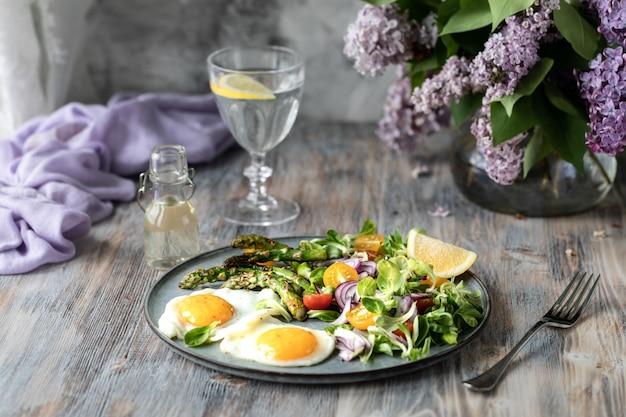 Een deel van veldsla met rode uien, gele tomaten, asperges en twee eieren op een plaat op een houten tafel.
