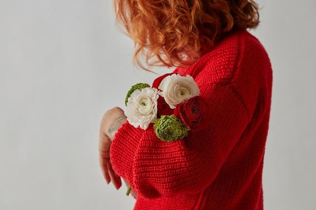Een delicaat boeket van veelkleurige bloemen van ranunculus wordt vastgehouden door een meisje in een rode gebreide trui op een grijze achtergrond met een kopie van de ruimte. moederdag cadeau