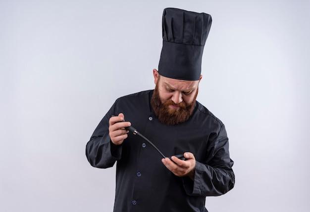 Een denkende bebaarde chef-kok in zwart uniform die zwarte pollepel met twee handen vasthoudt en ernaar kijkt op een witte muur
