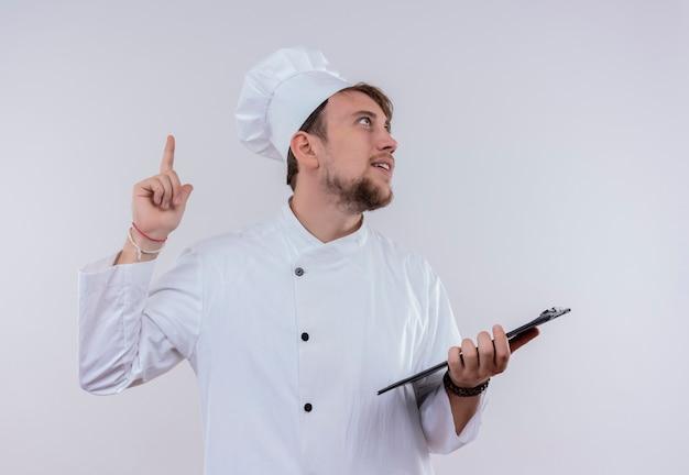 Een denkende jonge, bebaarde chef-kokman met een wit fornuisuniform en een hoed die omhoog wijst terwijl hij een lege map op een witte muur houdt