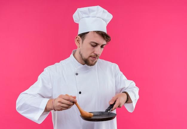 Een denkende jonge bebaarde chef-kokmens in wit uniform die koekenpan met houten lepel houdt terwijl hij op een roze muur staat
