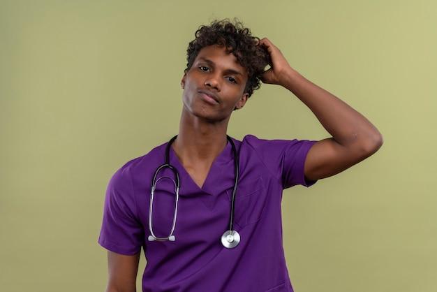 Een denkende jonge knappe donkere arts met krullend haar in violet uniform met een stethoscoop die de hand op het hoofd houdt terwijl hij op een groene ruimte is
