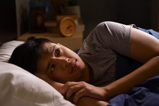 Een depressieve jongeman die lijdt aan slapeloosheid die in bed ligt