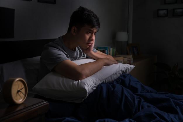Een depressieve jongeman die lijdt aan slapeloosheid, zittend in bed