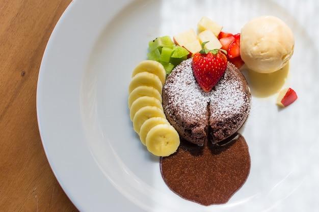 Een dessertgerecht dat chocoladelava heet, omvat vanille-ijs, banaan-kiwi en appel
