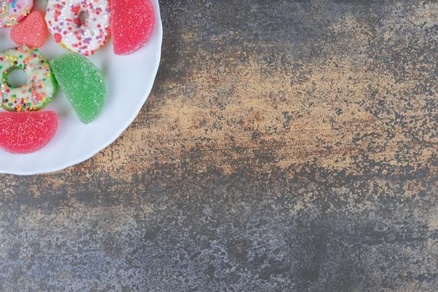 Een dessertportie van donuts en marmelades op houten oppervlak
