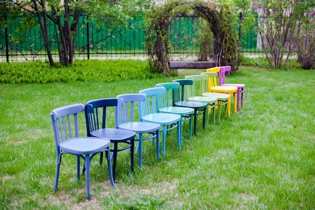 Een diagonale rij regenboog houten stoelen op een groen gazon in het park dat zich voorbereidt op een familiefeest op ...