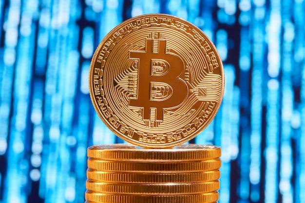 Één die bitcoin op rand op stapel gouden bitcoins met vaag blauw kring op achtergrond wordt geplaatst.