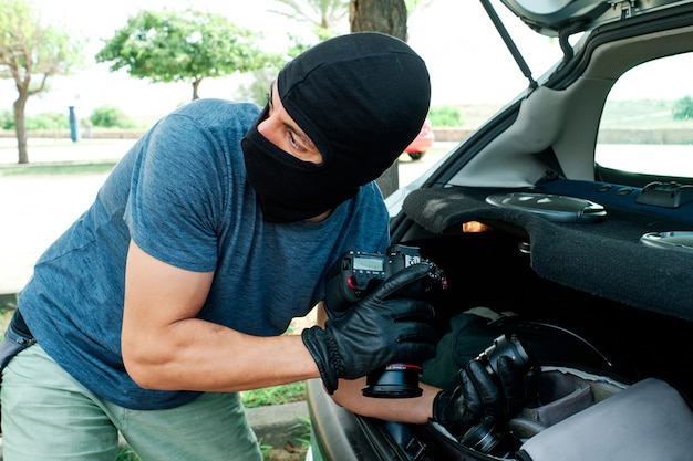Een dief met een masker dat fotografie-apparatuur en lenzen uit een auto steelt