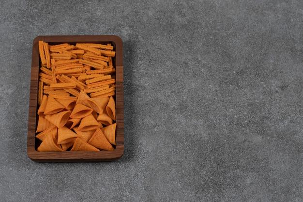 Een dienblad met gedroogd brood en maïsspaanders op het marmeren oppervlak