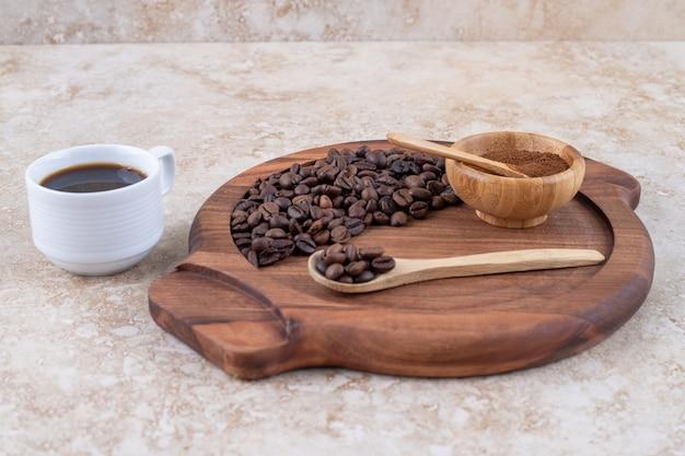 Een dienblad met gemalen en hele koffiebonen naast een kopje koffie