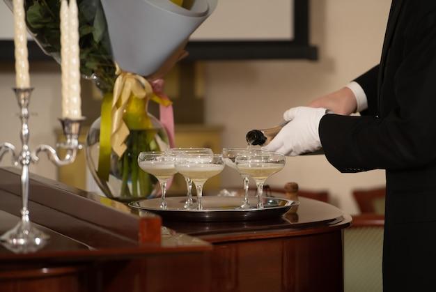 Een dienblad met glazen champagne en een fles mousserende wijn.