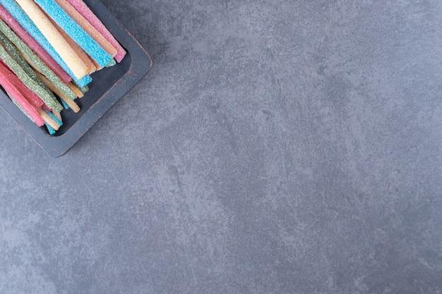 Een dienblad met jelly sticks op marmeren tafel.