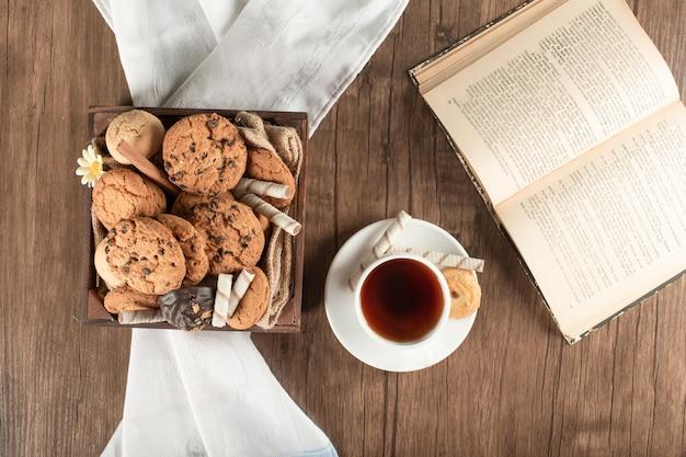 Een dienblad met koekjes en een kopje thee. bovenaanzicht
